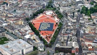 Das grösste Plakat der Welt wirbt für ein bedingungsloses Grundeinkommen: Aus der Helikopterperspektive sieht die 8000 Quadratmeter grosse  Affiche auf der Plaine de Plainpalais in Genf winzig klein aus.