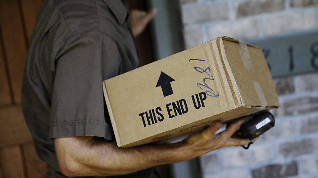 Ein UPS-Fahrer bringt ein Paket an die Haustüre: Zu Weihnachten braucht es viel mehr dieser Fahrer. UPS stellt deshalb 95'000 Aushilfen ein.