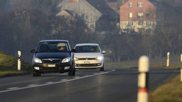 Autos mit eingeschaltetem Licht auf einer Strasse im Kanton Waadt