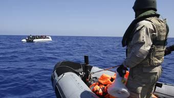 Ein belgischer Soldat fährt zu einem Boot mit Flüchtlingen, um diese in Sicherheit zu bringen. (Archiv)
