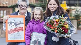 """Der Kinobesuch hat sich gelohnt: Filmproduzent Peter Reichenbach (links) überreichte Nadine und Gabriela Holdener einen Blumenstrauss und ein Geschenk. Mutter und Tochter teilen sich den Preis für den 200'000sten Besucher von """"Schellen-Ursli""""."""