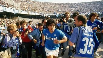 Alle Augen und Linsen sind auf ihn gerichtet: Diego Maradona läuft Mitte der 80er Jahre vor über 80 000 frenetischen Fans im Stadion San Paolo in Neapel ein.