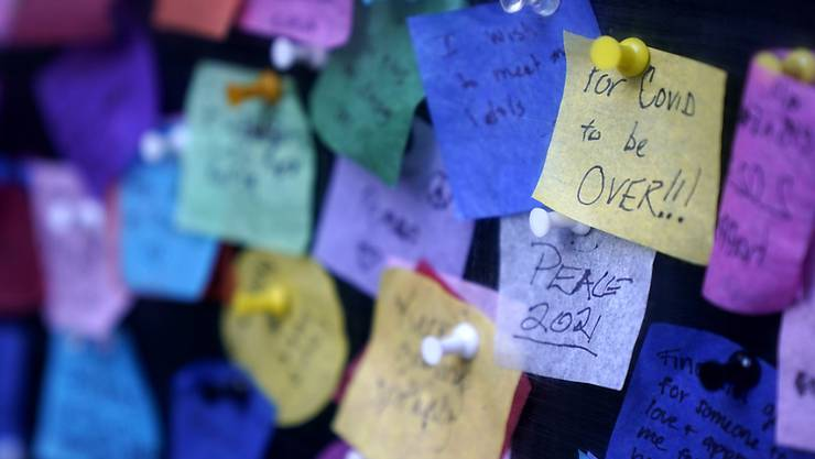 Botschaften, die Menschen auf buntes Papier geschrieben haben, sind am Times Square zu sehen. Foto: Seth Wenig/AP/dpa