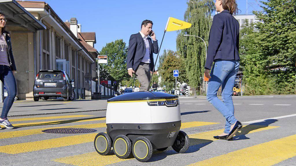 In Zukunft eventuell ein gewohntes Bild: Lieferroboter der Post auf einem Fussgängerstreifen.
