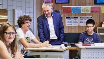 Bildungsdirektor Alex Hürzeler im fröhlichen Austausch mit Schülerinnen und Schülern einer altersdurchmischten Klasse der Tagesschule Zeka in Aarau