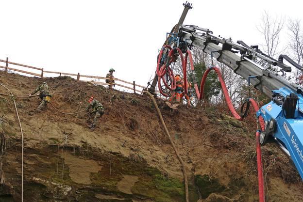 Angeseilt rammen Felstechniker bis zu sechs Meter lange Anker in den Sandsteinhang.