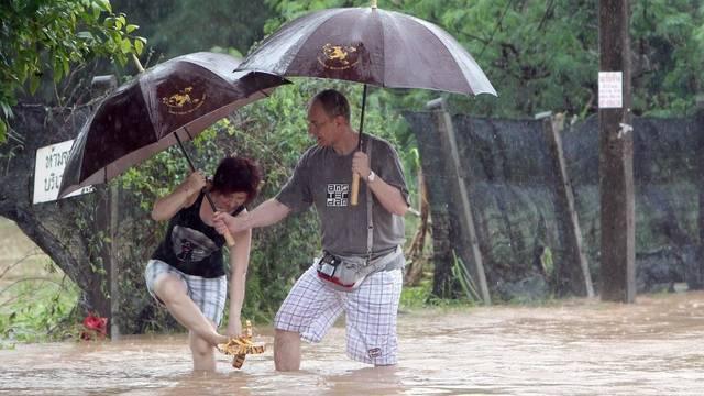 Zwei Touristen waten durch das knietiefe Wasser in Koh Samui