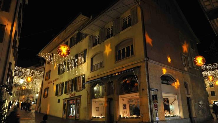 Lichterbögen wie Tannäste über der Gasse und Kugeln, die Sterne auf die Fassaden projizieren.