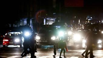 Passanten in Caracas überqueren einen Fussgängerstreifen im Dunkeln, nachdem wegen eines landesweiten Blackouts auch die Strassenbeleuchtung ausgefallen war.