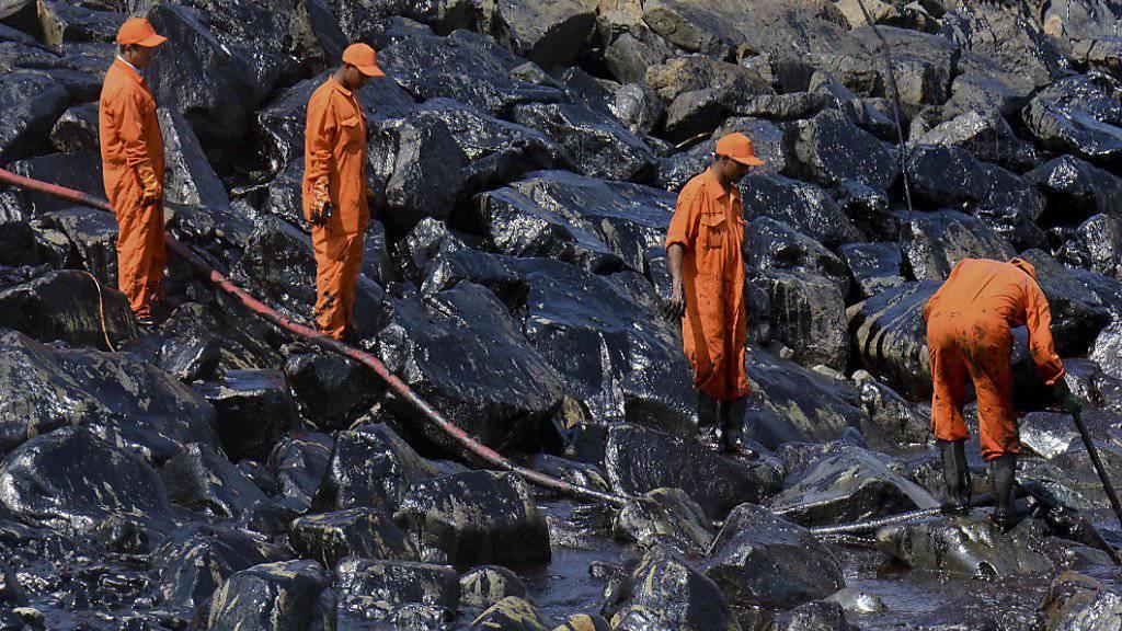 Helfer versuchen, die Küste vom Öl zu befreien.