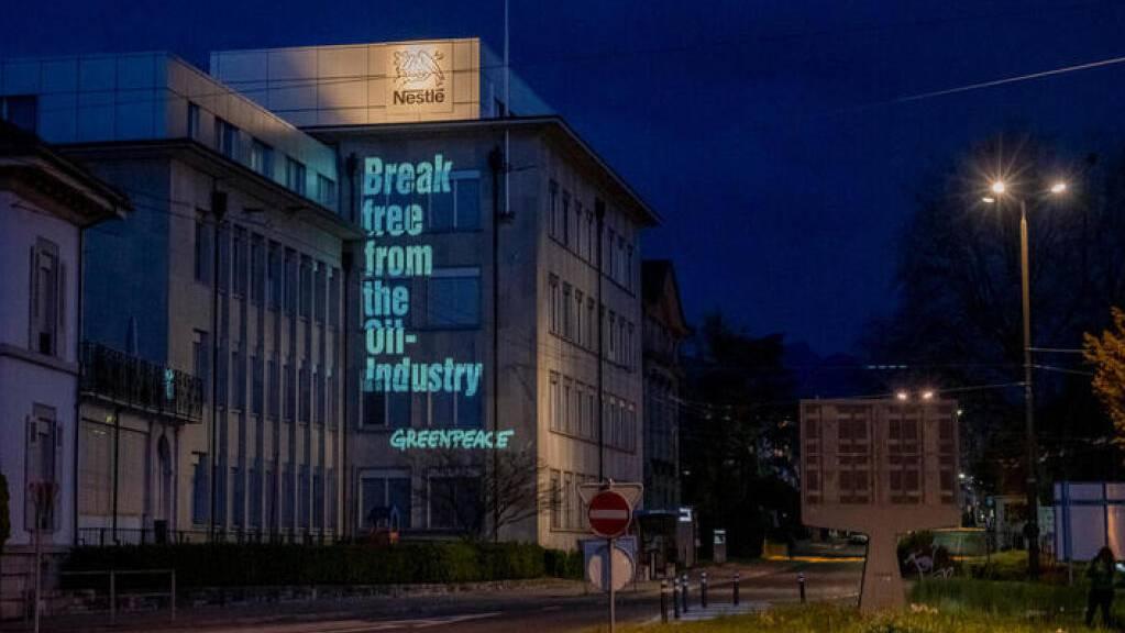 Die Umweltorganisation Greenpeace hat ihre Forderungen an die Fassade eines Nestlé-Betriebes in La-Tour-de-Peilz projeziert. (Bild: Greenpeace)