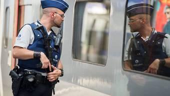 Ein belgischer Polizist kontrolliert in Brüssel einen Personenzug. (Archivbild)