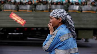 Eine Uigurin beobachtet in der Stadt Urumqi in der Provinz Xinjiang eine Parade der chinesischen Polizei. Nir Elias/REUTERS