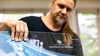 Marcel Hartmann bearbeitet eine Plexiglasscheibe für einen Kunden aus dem Gastgewerbe.