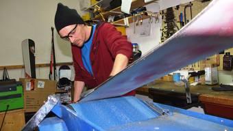 Der Schnee kann kommen: Alvin de Groot vom No Limit in Brugg präpariert in der Werkstatt ein Snowboard.
