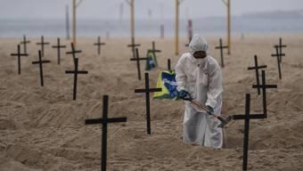 Ein brasilianischer Aktivist gräbt am berühmten Strand Copacabana symbolische Gräber für die Coronatoten.