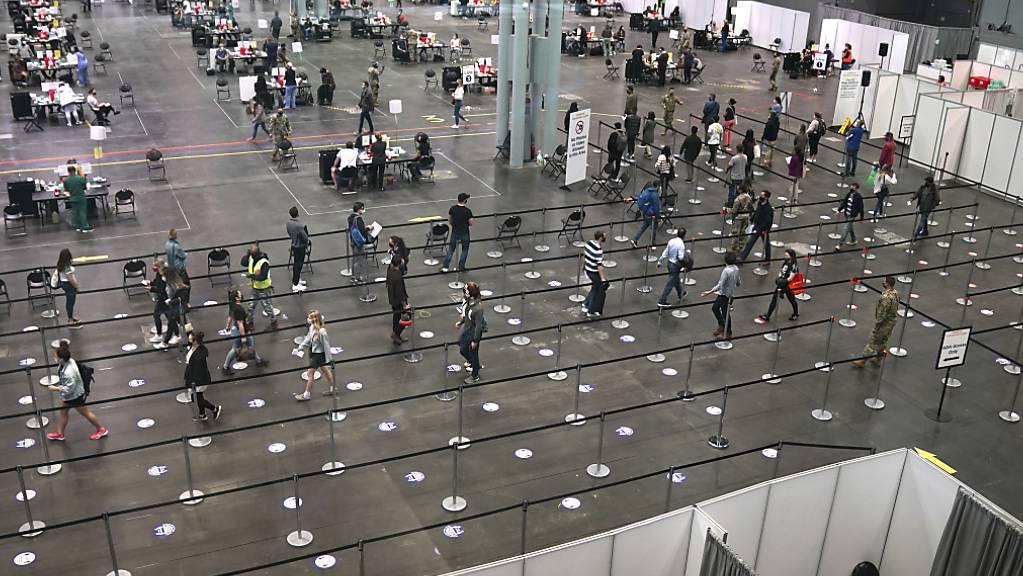 Menschen warten im Jacob K. Javits Convention Center in New York auf ihre Corona-Impfung. Foto: Timothy A. Clary/Pool AFP/AP/dpa