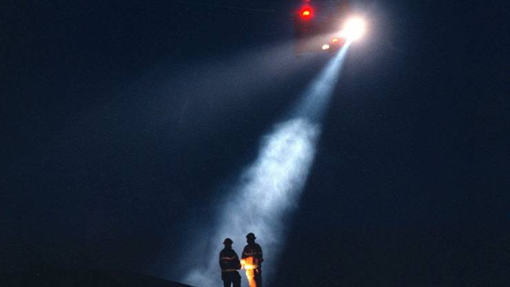 Feuerwehrleute und ein Such- und Rettungshubschraubers auf der Suche nach Überlebenden oder Opfern