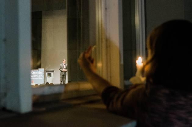 Juso-Aargau-Präsidentin Mia Kicki Gujer zeigt während der Mahnwache Christoph Mörgeli durchs Fenster den Stinkefinger.