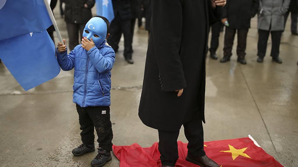 Auf der chinesischen Fahne stehend protestiert ein Demonstrant in Istanbul gegen den Besuch des chinesischen Außenministers Wang in der Türkei. Foto: Emrah Gurel/AP/dpa