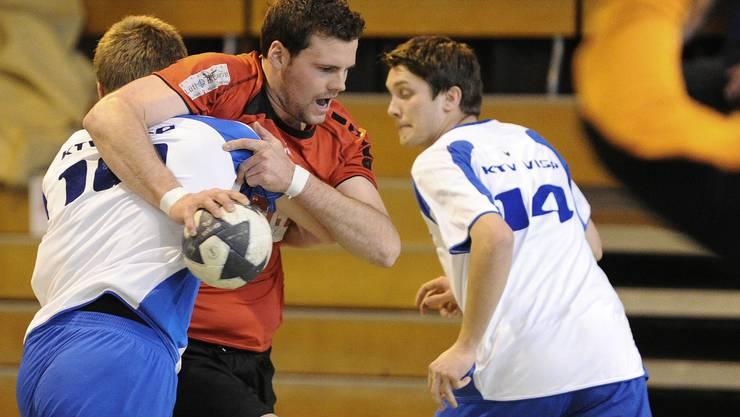 Der Solothurner Dirk Wuergler (M) im Kampf um den Ball gegen die Visper  Florin Widmer (L) Thibaud Mendis (R) waehrend des 1