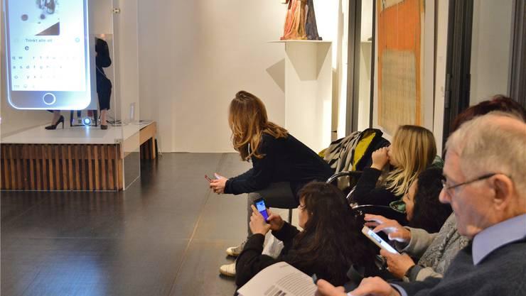 Das Publikum kommuniziert via Handy mit Simona Hofmann (in der Glasbox, l.).