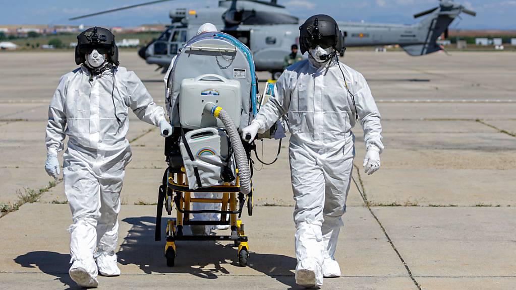 Zwei Soldaten schieben nach einer Übung auf dem Luftwaffenstützpunkt in Torrejon de Ardoz eine Bahre. Mehr als 90 000 spanische Militärangehörige haben seit Beginn der Corona-Krise in Spanien in Einsätzen zur Desinfektion, zur Unterstützung in Krankenhäusern, zur Überführung von Kranken und Toten und von medizinischem Material gearbeitet. Foto: Ricardo Rubio/EUROPA PRESS/dpa