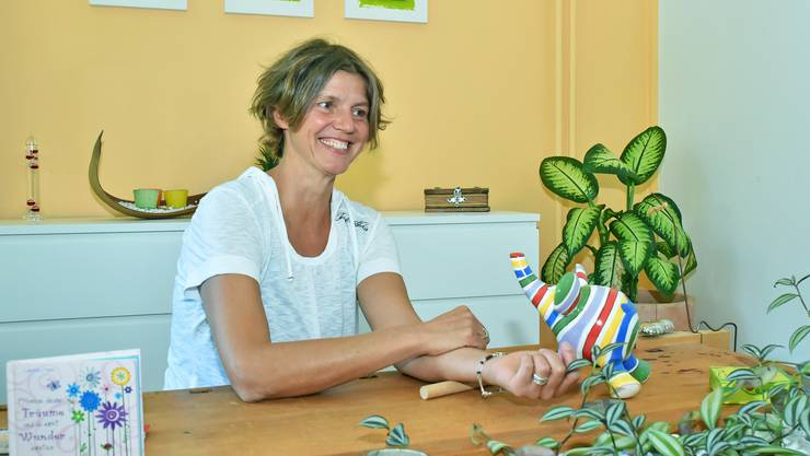 Anita Geiser zeigt eine Übung in ihrer Praxis. Das runde Hölzchen dient zur Bewegungsarbeit mit den Klienten.