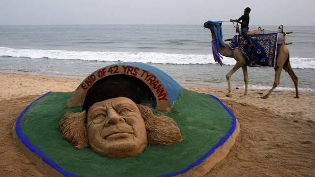 Eine Sandskulptur zum Ende der Gaddafi-Ära an einem Strand in Indien