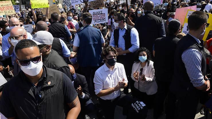 Kanadas Premierminister Justin Trudeau (Bildmitte) geht an einer Protestveranstaltung in Ottawa als Zeichen der Solidarität auf die Knie.