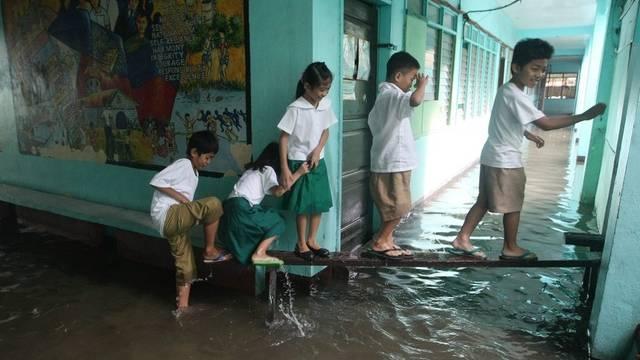 Schulkinder in den Philippinen versuchen dem Wasser zu entkommen