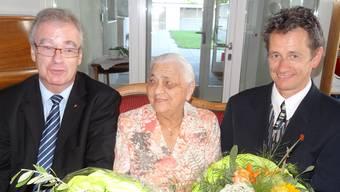 Die 100-jährige Maria Bürgi-Pfisterer nimmt Glückwünsche und Blumen entgegen von Daniel Vulliamy, Leiter Rheinfelder Stabsdienste/Stadtmarketing (links), und Stadtweibel Marcel Hauri. – Foto: chr