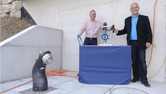 Gemeindeammann Willy Schürch (rechts) und Gemeinderat Roland Oeschger öffnen den symbolischen Schieber beim neuen Wasserreservoir in Münchwilen (links der Saughydrant für die Feuerwehr). – Foto: chr