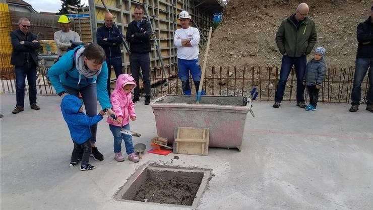 Vivien (2) und Eric (1) packen mit ihrem Mami an, um an der Grundsteinlegung in Möriken eine Metallkiste einzubetonieren.