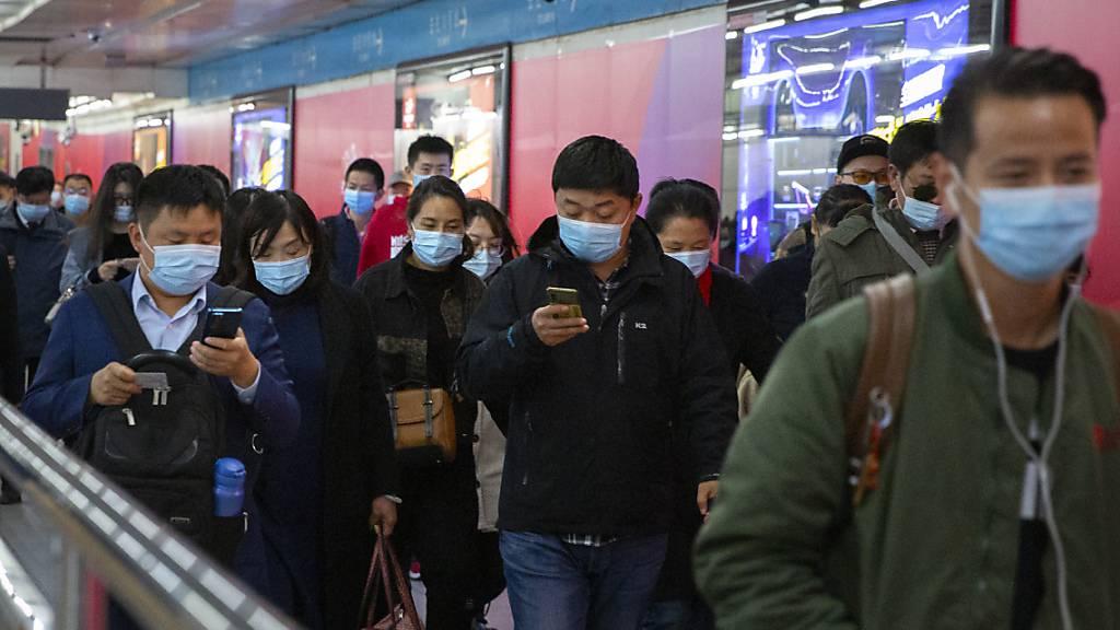 Pendler schauen auf ihre Smartphones, während sie durch eine U-Bahn-Station in Peking gehen. Gut ein Jahr nach dem Ausbruch gilt das Coronavirus in China als so gut wie besiegt. Selbst in der besonders betroffenen Metropole Wuhan ist von Krise kaum noch etwas zu spüren. (Archiv)