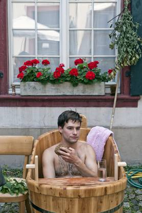 Philippe Waller geniesst das warme Bad im historischen Holzzuber. 20 Minuten darf er sitzen bleiben, danach gibt's eine Abkühlung.