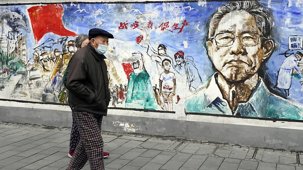 Anwohner gehen in der zentralchinesischen Stadt Wuhan, in der das Coronavirus zum ersten Mal nachgewiesen wurde, an einem Wandgemälde mit dem Titel «Erinnerungen» vorbei. Foto: Ng Han Guan/AP/dpa