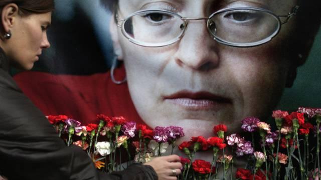 Frau steckt eine Blume vor Porträt von Anna Politkowskaja (Archiv)