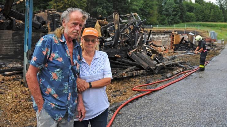Alfred Venez und seine Partnerin Ruth von Gunten stehen vor dem niedergebrannten Lebenswerk, das Venez vor 36 Jahren als Ruine erworben und wieder aufgebaut hatte.