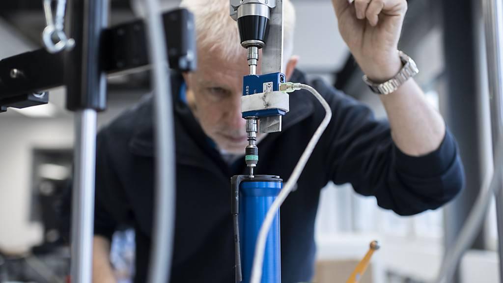 Ein Mitarbeiter der Zuger Firma Bossard testet Schraubverbindungen am Verschraubungsprüfstand: Die Aktionäre des Unternehmens erhalten eine höhere Dividende. (Archivbild)