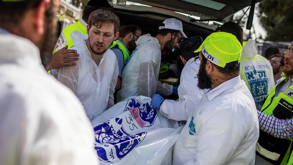 Israelische Rettungskräfte tragen den Leichnam eines Opfers, an der jüdisch-orthodoxen Pilgerstätte des Berges Meron, wo Dutzende von Gläubigen bei einer Massenpanik während des jüdischen religiösen Festes Lag BaOmer im Norden Israels getötet wurden.