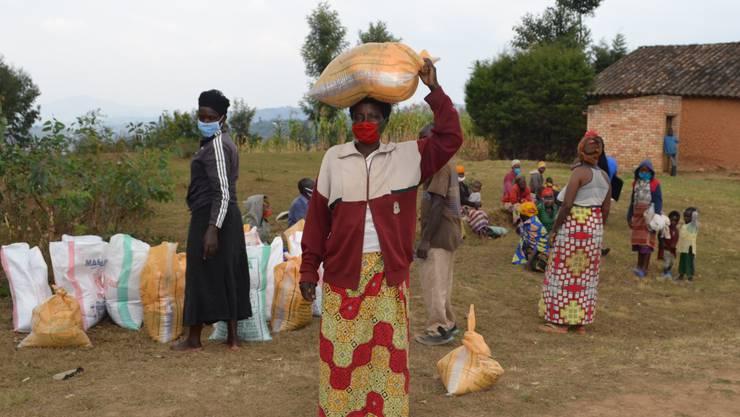 Unter strengen Auflagen werden in Ruanda Lebensmittelpakete an die ärmsten Familien verteilt.