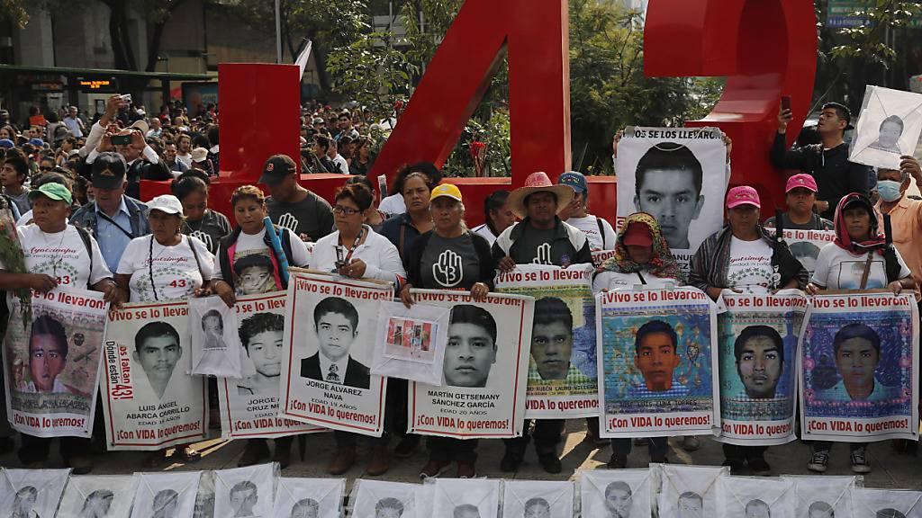 ARCHIV - Angehörige der 43 vermissten Lehramtsstudenten halten 2019 bei einem Protestmarsch Porträts der Vermissten. Foto: Marco Ugarte/AP/dpa