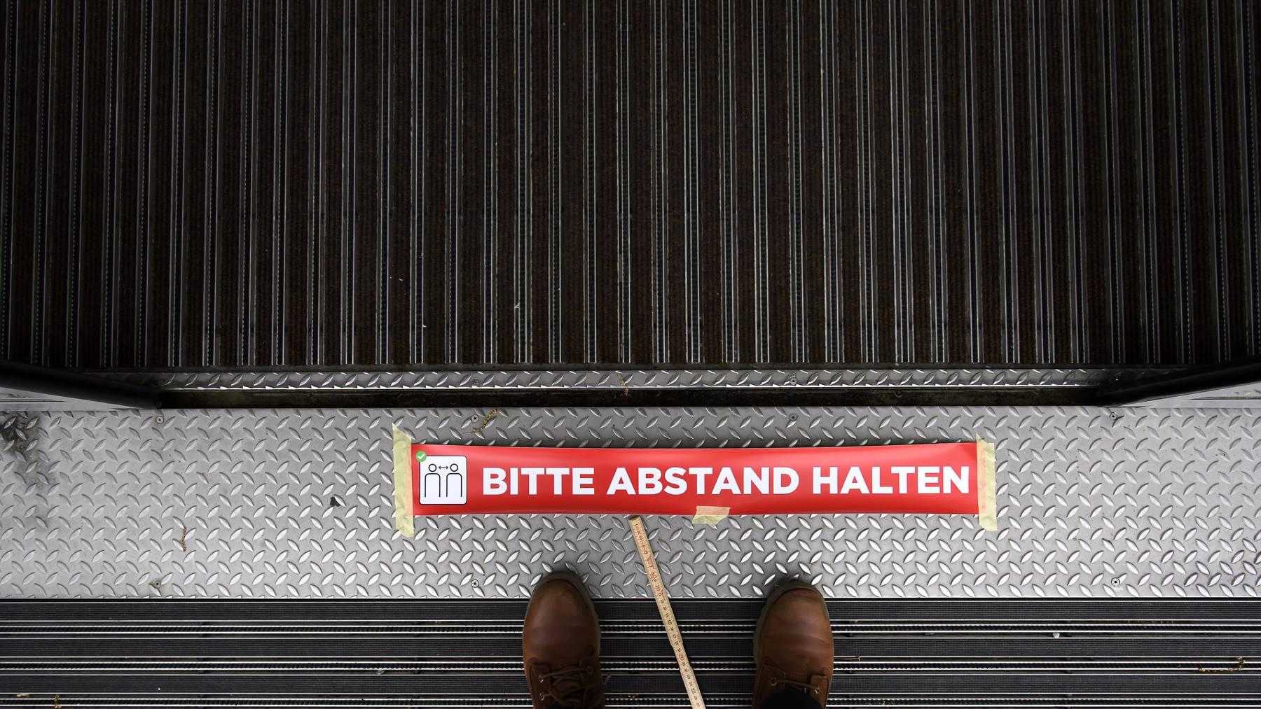 Ein Mitarbeiter bringt in Bern in der Coronakrise Aufkleber des Bundesamts für Gesundheit zur Einhaltung des Social Distancing an.