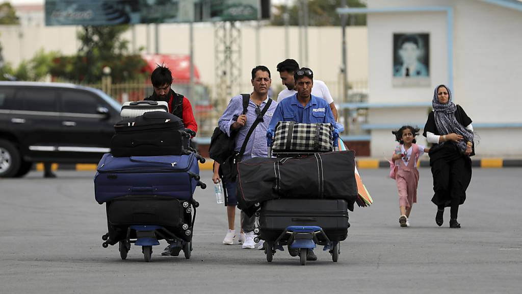 Passagiere gehen zum Abflugterminal des internationalen Flughafens Hamid Karzai in Kabul, Afghanistan. Da die afghanische Hauptstadt von einer Taliban-Offensive umzingelt ist, gibt es für diejenigen, die vor dem Krieg fliehen, zunehmend nur noch einen Weg nach draußen.
