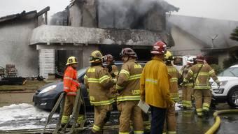 Die Feuerwehr löscht den Brand des Hauses, das beim Flugzeugabsturz in Flammen aufging.