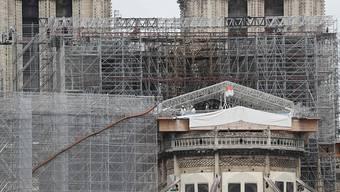 Arbeiter auf einer Plattform demontieren beschädigte Gerüstteile an der Kathedrale Notre-Dame. Foto: Ludovic Marin/AFP/dpa