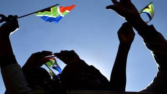 Besucher des Festes schwenken südafrikanische Flaggen