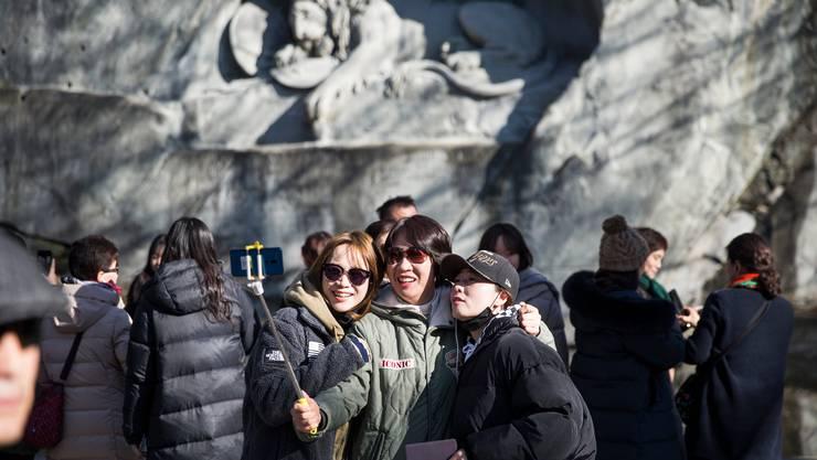 Eine Gruppe asiatischer Touristen vor dem Löwendenkmal in Luzern.