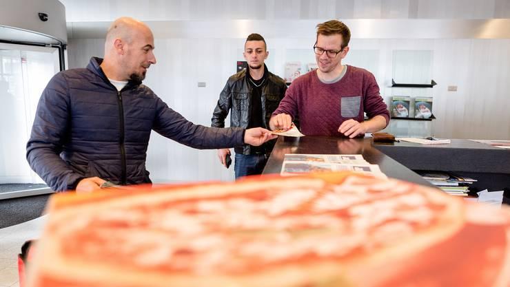 Martin Rupf, Ressortleiter des Badener Tagblatts, nimmt in der Empfangshalle des az-Gebäudes die Pizzas der Kuriere von den Pizzalieferdiensten «Trulli» aus Nussbaumen (l.) und «Mania» aus Rieden in Empfang.
